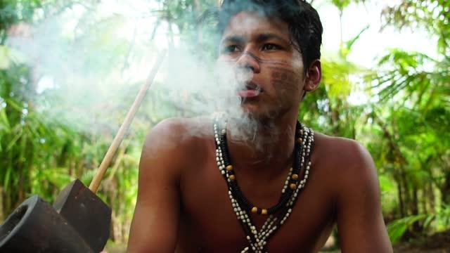 indigener mann aus tupi guarani stamm rauchen pfeifen im wald, brasilien - indianischer abstammung stock-videos und b-roll-filmmaterial