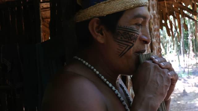 stockvideo's en b-roll-footage met inheemse mens die bamboefluit speelt - hoofddeksel