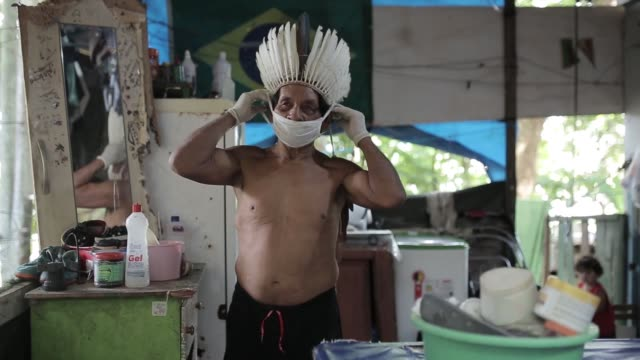 indigenous people continue to live in their traditional lifestyle in amazonas, the largest state of brazil, but they now wear protective masks and... - charity benefit stock videos & royalty-free footage