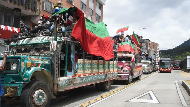 vídeos y material grabado en eventos de stock de indigenous people ride at the top of a 'chiva' while being part of a caravan to participate in a general strike against social and economic policies... - marchar