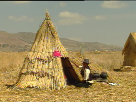 indigenous uros male in hat vest pushing in totorareeds on tee pee dwelling preincan culture peruvian andes lake titicaca native art - peruvian ethnicity stock videos & royalty-free footage