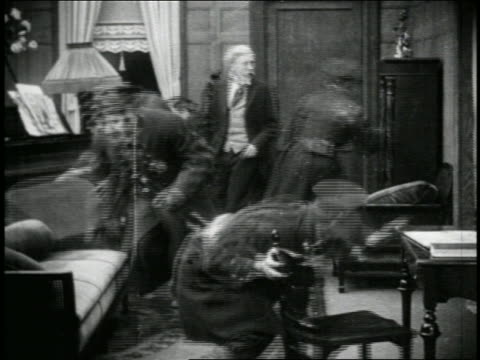 stockvideo's en b-roll-footage met b/w 1915 indignant senior man talking to group of keystone kops searching for something in room - 1915