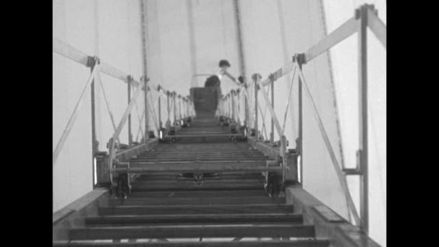 indistinct shot / shot from below of worker standing on tall ladder painting aluminum hull of airship uss macon above him / note exact year not known - airship stock videos & royalty-free footage