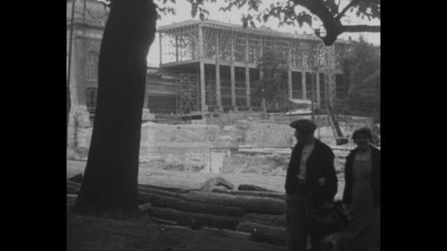 vidéos et rushes de indistinct shot / shot through fence of empty construction site and building under construction / striking construction workers on roof of building... - grève