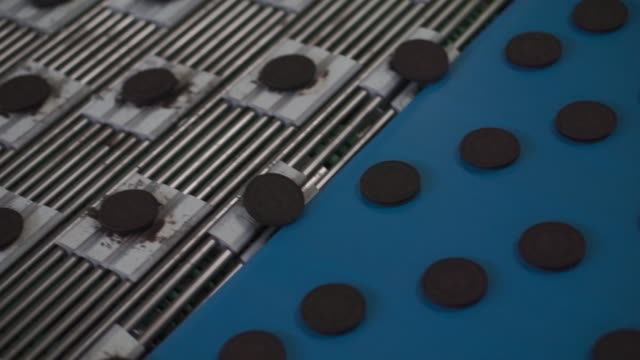 vídeos de stock, filmes e b-roll de individual parts for oreo biscuits move along a conveyor belt at the trostyanets confectionery plant, operated by mondelez international inc., in... - doces
