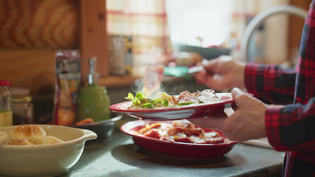 individual places food on their plate at a family gathering - putting stock videos & royalty-free footage
