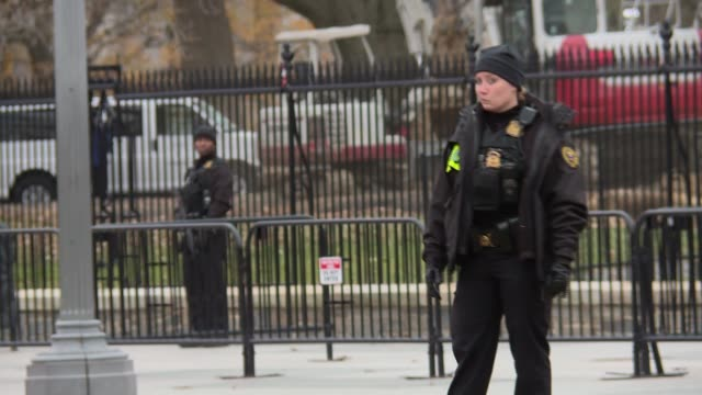 stockvideo's en b-roll-footage met individual secret service agents in uniform patrolling what was pennsylvania avenue pavement on the lafayette park side of the white house includes... - geheime dienstagent