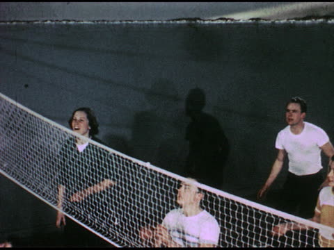 vidéos et rushes de individual shots of 50s teens playing volleyball/ each hits ball/ group as they play/ close shot of volleyball, fade out, in/ volleyball and net on... - fade out