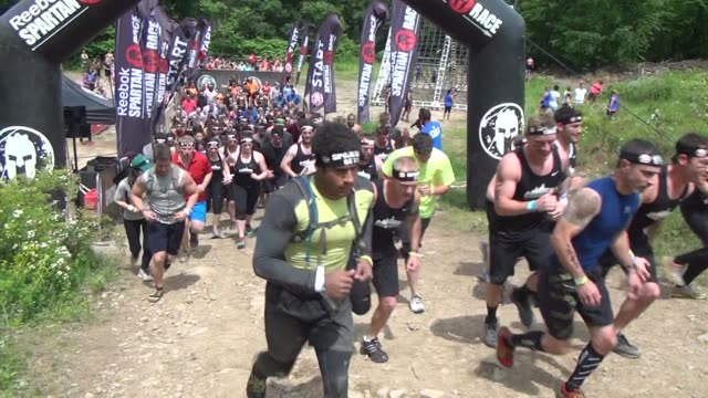 individuals and teams take on the challenge of obstacle racing mud barbed wire fire pits rope climbs - salmini stock videos & royalty-free footage