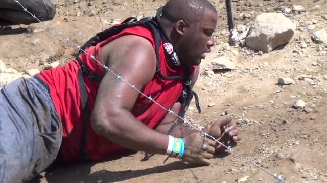 Individuals and teams take on the challenge of obstacle racing mud barbed wire fire pits rope climbs / Uphill under barber wire
