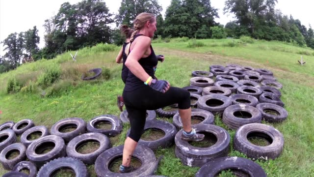 individuals and teams take on the challenge of obstacle racing mud barbed wire fire pits rope climbs / jump through tire maze - obstacle course stock videos & royalty-free footage