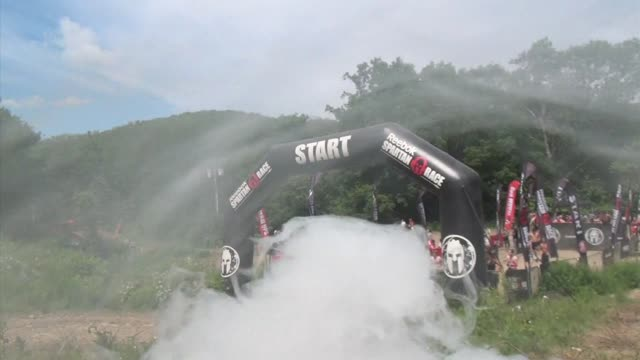 individuals and teams take on the challenge of obstacle racing mud barbed wire fire pits rope climbs / smoke bomb before the start - salmini stock videos & royalty-free footage