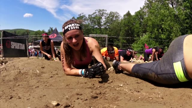 individuals and teams take on the challenge of obstacle racing mud barbed wire fire pits rope climbs crawling through mud under barber wire woman... - querfeldeinrennen stock-videos und b-roll-filmmaterial