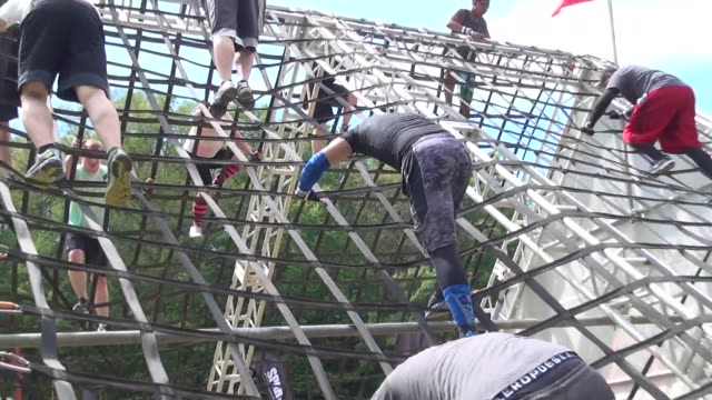 individuals and teams take on the challenge of obstacle racing mud barbed wire fire pits rope climbs / over and down rope maze - salmini stock videos and b-roll footage