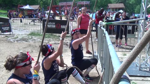 individuals and teams take on the challenge of obstacle racing mud barbed wire fire pits rope climbs / women pull on ropes - salmini stock videos and b-roll footage