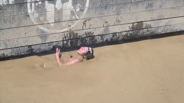 individuals and teams take on the challenge of obstacle racing mud barbed wire fire pits rope climbs / woman comes up from underwater - salmini stock videos and b-roll footage