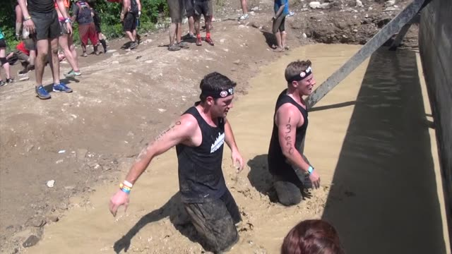 individuals and teams take on the challenge of obstacle racing mud barbed wire fire pits rope climbs / men go underwater to get past obstacle - salmini stock videos and b-roll footage