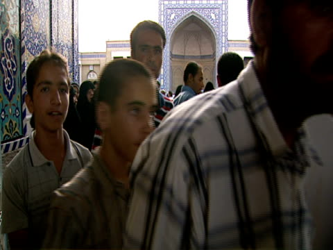 vidéos et rushes de individuals filtering through doorway of qom shrine while a man sings an arabic prayer / qom, iran - format vignette