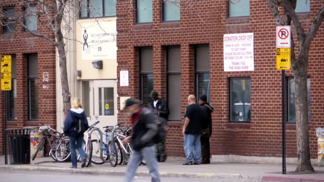 individuals gather outside of the road home salt lake community shelter and self sufficiency center in downtown salt lake city ut - self sufficiency stock videos and b-roll footage