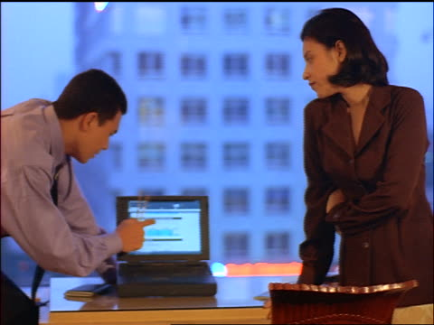 Indonesian businessman + businesswoman looking at laptop computer in hotel room / Jakarta