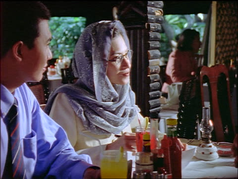 Indonesian (Muslim) couple at table in restaurant shaking hands with man / Jakarta