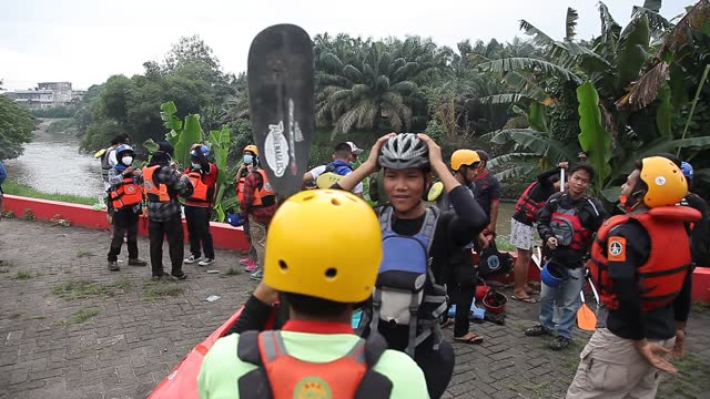indonesian environmental activists put on helmets in preparation to collect plastic waste that has pooled in the deli river basin during world... - albert damanik stock videos & royalty-free footage