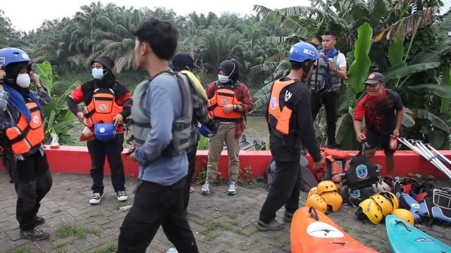 indonesian environmental activists put on life jackets in preparation to collect plastic waste that has pooled in the deli river basin during world... - albert damanik stock videos & royalty-free footage