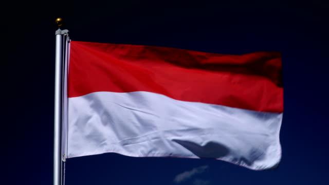 4K: drapeau indonésien sur mât devant extérieur bleu ciel (Indonésie)