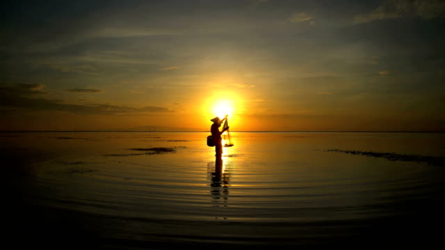 indonesian male fishing on the coastline at sunrise - headwear stock videos & royalty-free footage