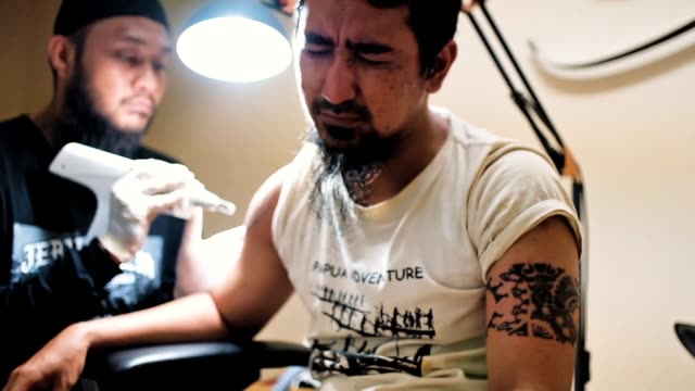 vídeos de stock, filmes e b-roll de indonesian tattoo remover sandi widodo does a brisk business zapping sin from skin at bargain basement prices - zapear