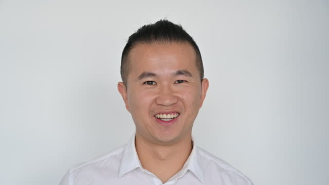indoor headshot of east asian man in white open collar shirt - hair back stock videos & royalty-free footage