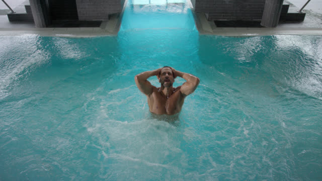 indoor pool area in hotel day SPA – tanned attractive sporty man in his 30s with short dark hair in turquoise swim shorts, jumps splashing into the blue thermal water, comes up and swims out of frame – top shot locked camera