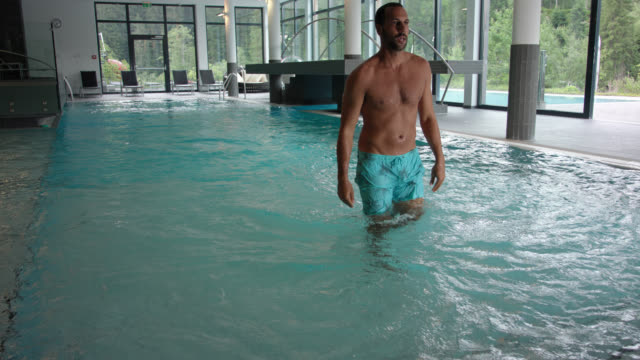 indoor pool area in hotel spa with panorama windows during day – man in his 30s with short dark hair and trimmed beard wears turquoise swim shorts, swimming crawl for training towards the camera and walking out of the water and frame. - swimming shorts stock videos & royalty-free footage