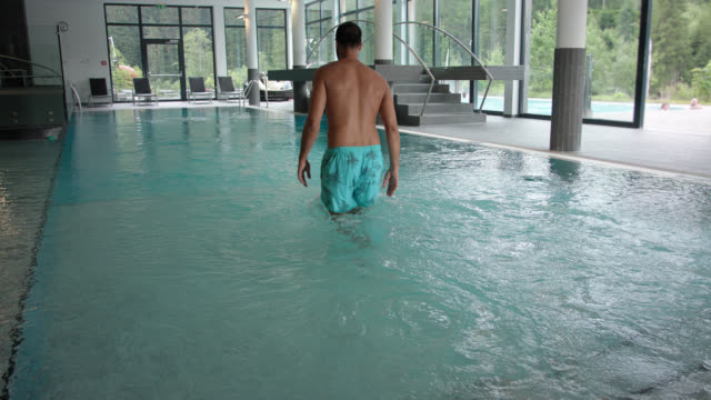 indoor pool area in hotel spa with surrounding panorama windows during day – man in his 30s with short dark hair in turquoise swim wear walks into the empty blue thermal water. - thermal pool stock videos & royalty-free footage