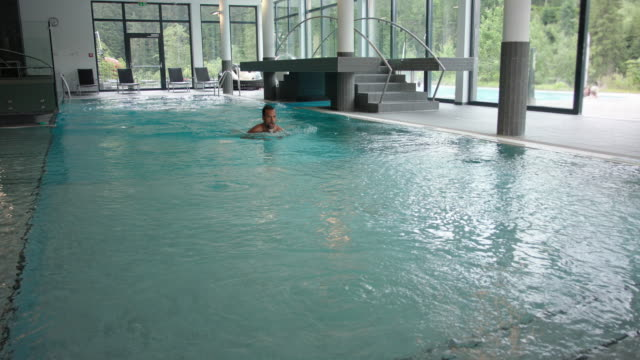 indoor pool area in hotel SPA with surrounding panorama windows during day – man in his 30s with short dark hair in turquoise swim wear diving into blue water, swimming breast-stroke towards camera, walking out of the water and exiting the frame