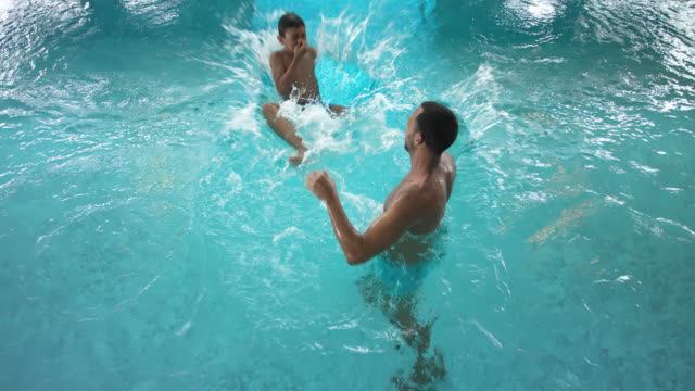 indoor pool area in hotel – tanned attractive sporty man in his 30s with short dark hair having fun together with his 8 years old little boy, father tossing his son and the child splashing into the turquoise blue thermal water - 30 39 years点の映像素材/bロール