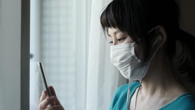 窓の外を見て外科用マスクを着用したアジアの女性の屋内肖像画 - 東アジア点の映像素材/bロール