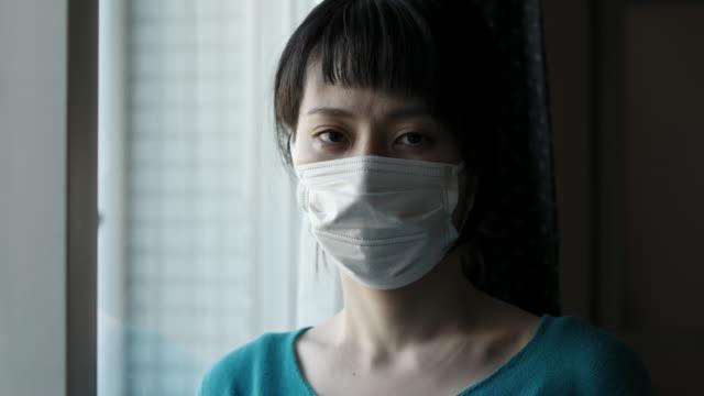 窓の外を見て外科用マスクを着用したアジアの女性の屋内肖像画 - 衛生管理点の映像素材/bロール