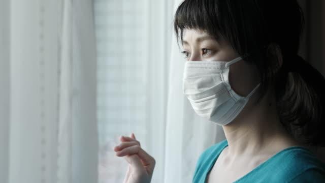 窓の外を見て外科用マスクを着用したアジアの女性の屋内肖像画 - covid 19点の映像素材/bロール
