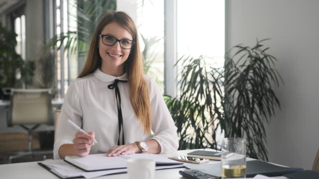 indoor portrait of smiling caucasian businesswoman in office - blocco per appunti video stock e b–roll