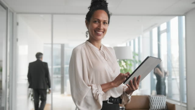 indoor portrait of smiling hispanic businesswoman in office - hand an der hüfte stock-videos und b-roll-filmmaterial