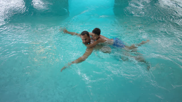 indoor swimming pool area – tanned man in his 30s with short dark hair spending time together with his 8 years old little boy, father swimming in the turquoise blue thermal water while pulling his son hugging on his back - 30 39 years点の映像素材/bロール
