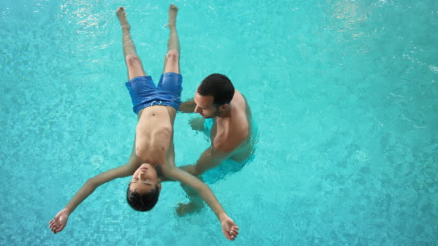 indoor swimming pool – tanned man in his 30s with short dark hair spends time together with his pre-adolescent 8 years old son in the turquoise blue thermal water, the single father does aqua balance with his child, kid is floating in the water – top shot - 30 39 years点の映像素材/bロール