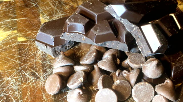 Indulge yourself in tasty Chocolate on Cutting board in direct light Dark Chocolate Bars and Chocolate Kisses