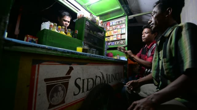industri jamu dan farmasi sido muncul advertisement is displayed on the front of a street stall where a vendor serves his customers in jakarta... - sachet stock videos & royalty-free footage