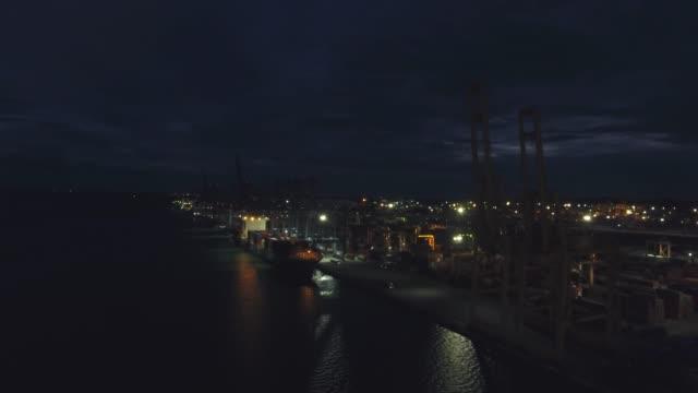 porto logistico di navi industriali e container di notte, video aereo - porto marittimo video stock e b–roll