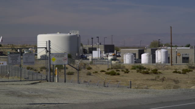 ws pan industrial area and canal behind chain link fence, palmdale, california, usa - palmdale stock videos and b-roll footage
