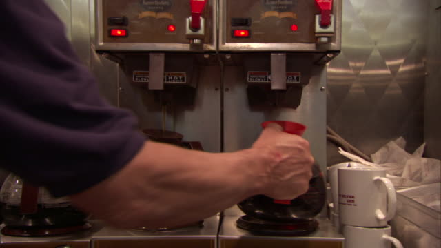 MS Industrial coffee machines at restaurant/ Hand gripping coffee pot and carrying it away/ Reno, Nevada