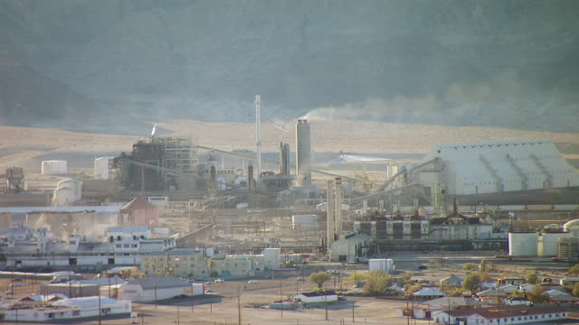 ws aerial pov industrial complex billowing smoke in searles valley with mountains in background / trona, california, united states - valley stock videos & royalty-free footage