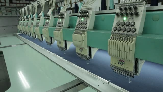 Industrial embroidery machines operate at a Rajlakshmi Cotton Mills Ltd garment factory in Kolkata West Bengal India on Monday Dec 25 An employee...